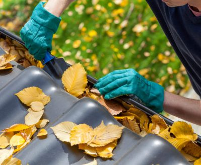 Man cleaning the gutter for fall